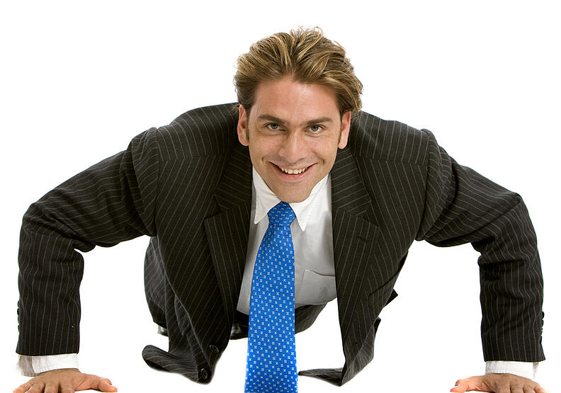 Business man doing push-ups isolated over white