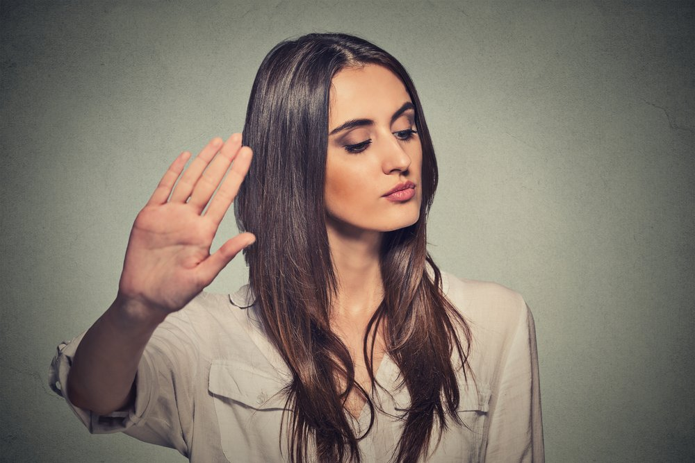 Closeup portrait young annoyed angry woman with bad attitude giving talk to hand gesture with palm outward isolated grey wall background. Negative human emotion face expression feeling body language-1
